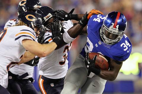 Giants running back David Wilson is brought down by Geno Hayes, Charles Tillman and Craig Steltz during the first quarter.