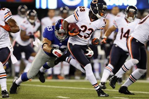 Devin Hester runs out of a tackle by Giants linebacker Chase Blackburn during the first quarter.