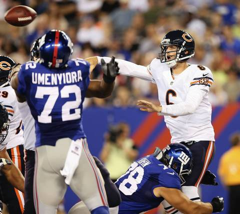QB Jay Cutler gets rid of the ball as the Giants' Markus Kuhn pressures him.