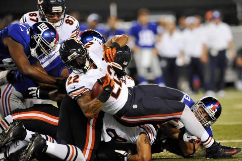 Matt Forte pushes forward on a rush attempt during the first half.