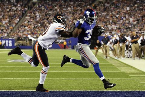 Giants running back Andre Brown scores a touchdown in front of Major Wright during the second quarter.
