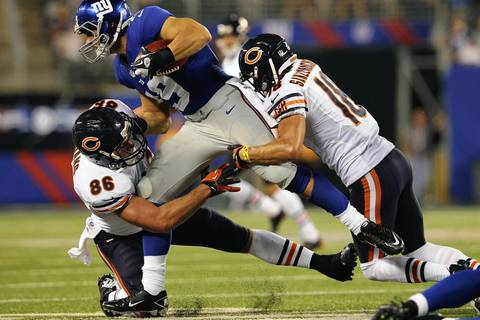 Giants wide receiver David Douglas is brought down by Kyle Adams and Dane Sanzenbacher during the fourth quarter.