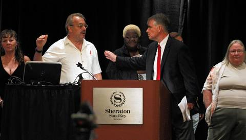 State GOP chairman Pat Brady tries to usher a group of minimum wage protesters off the stage during the Illinois delegation breakfast at the Sheraton Sand Key Resort in Clearwater Beach, Fla. before the Republican National Convention.