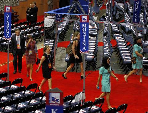People arrive on the floor and are reflected on a shiny wall at the Tampa Bay Times Forum on the first day the Republican National Convention.