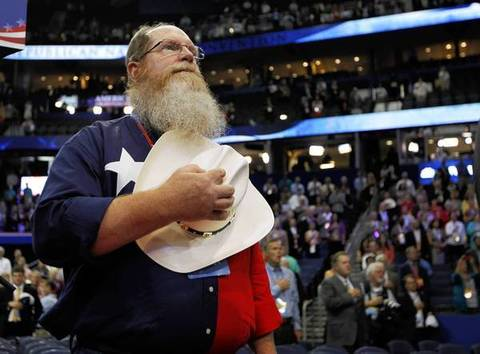 A Texas delegate listens to the Star Spangled Banner at the Tampa Bay Times Forum in Tampa, Fla. on the first full day at the Republican National Convention.