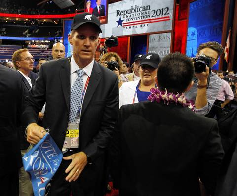 A man tears a Ron Paul sign away from a supporter on the convention floor at the Tampa Bay Times Forum in Tampa, Fla., on the first full day of the Republican National Convention.