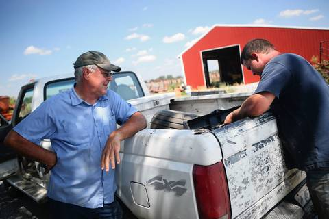 Wendell, left, and Jordan Norris take a break from cutting and bagging corn for silage for cattle near Waltonville in Jefferson County.