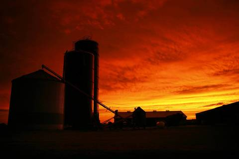 A farm near Baldwin in Randolph County is silhouetted by a vibrant sunset.
