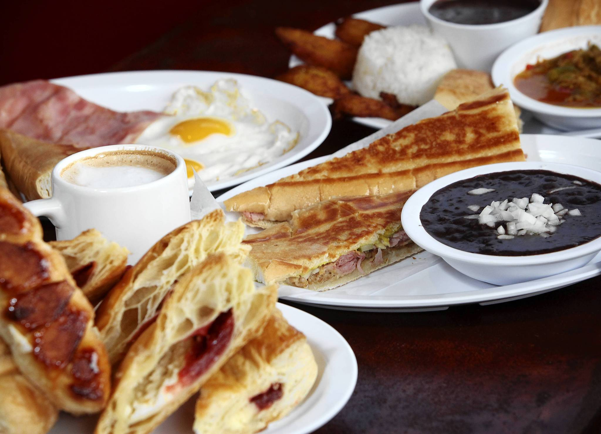 An assortment of food from Yaya's Cuban Cafe & Bakery: ropa vieja, Cuban sandwich, pastries and breakfast items.