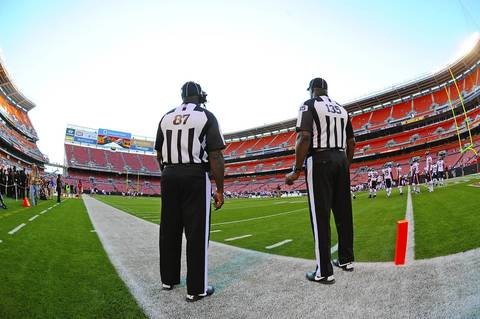 Replacement referees stand on the sideline.
