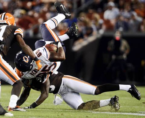 Bears tight end Brandon Venson is tackled by Browns cornerback Tashaun Gipson during the first half.