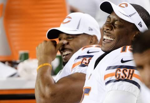 Matt Forte (left) and Brandon Marshall laugh on the bench.