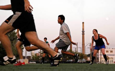 Soccer players play a pick up game at Benito Juarez Community Academy near the Midwest Generation Fisk Generating Station in Chicago's Pilsen neighborhood.
