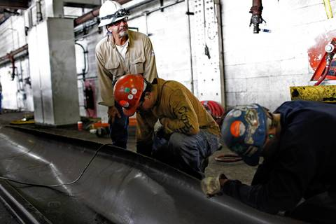 A Midwest Generation worker, standing, and other operators who are working for Midwest Generation's Fisk Generating Station work on cleaning coal built up on the coal bunkers one day before the plant permanently closed.