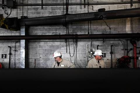 Midwest Generation workers clean coal bunkers near the conveyer that brings coal into the Midwest Generation Fisk Generating Station.