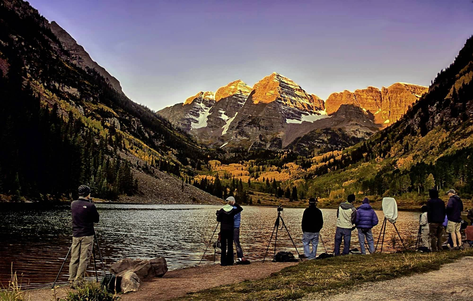 Photographers gather at sunrise at Maroon Lake, Colo., to shoot the Maroon Bells, framed by shadowed lateral ridges.