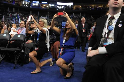 Delegates take photos on the floor of the convention.