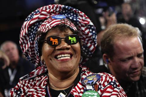 Delegate Julia Hicks from Westminster Colorado is all smiles in her donkey sunglasses. First Lady Michelle Obama arrives on the stage to speak at the Democratic National Convention.