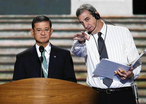 U.S. Secretary of Veterans Affairs Eric Shinseki, left, stands at the podium with stage manager David Cove during a walk-through on day two of the Democratic National Convention at Time Warner Cable Arena in Charlotte, North Carolina.