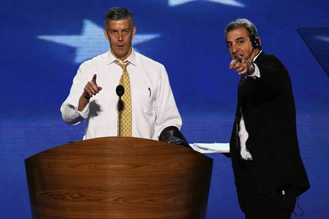 U.S. Secretary of Education Arne Duncan and stage manager David Cove walk through the plan for the night during day two of the Democratic National Convention.
