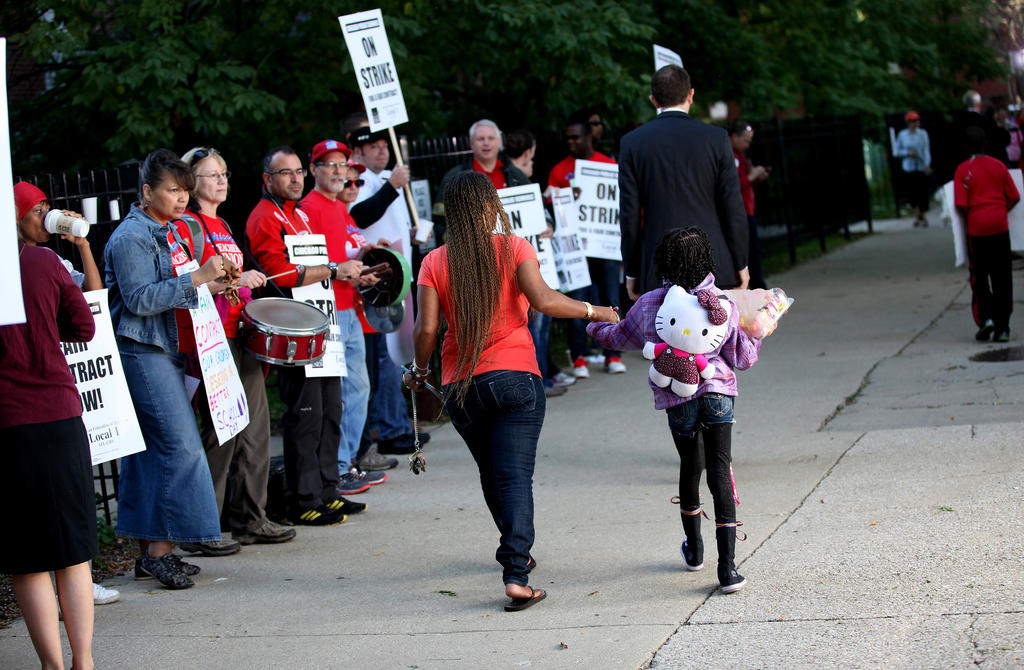 Parents and children walk past picketing teachers outside Ray Elementary School in the Hyde Park neighborhood of Chicago. Ray is one of the open schools for the displaced students.