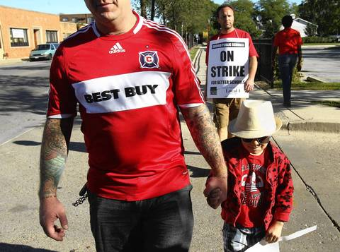Matt Flanagan, the husband of a teacher at Northside College Preparatory High School in Chicago, walks the picket line with his two-year old son J.D. Psychology teacher Charles Milbert walks behind.
