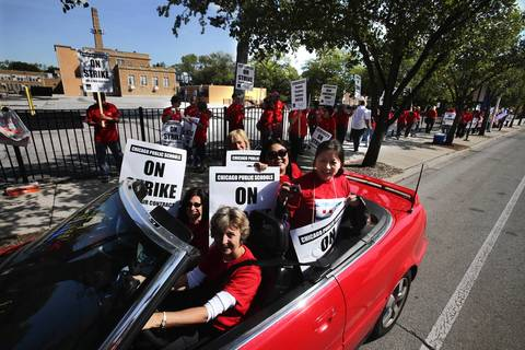 Teachers at Jamieson Elementary School on Bryn Mawr Avenue in Chicago walk the picket line in front of their school as some of their fellow teachers, who are finished picketing, drive by in an appropriately red convertible.