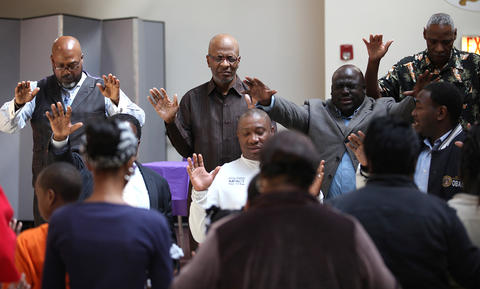 Bishop Larry Trotter, second from left, and other South Side and West Side Pastors pray over students at Sweet Holy Spirit Church in Chicago. CPS students came to the church for a Safe Haven during the strike.