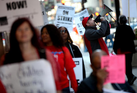 Nate Gunderson leads Chicago Teachers Union members in a chant while they picket outside the CPS headquarters in Chicago on day two of their strike.