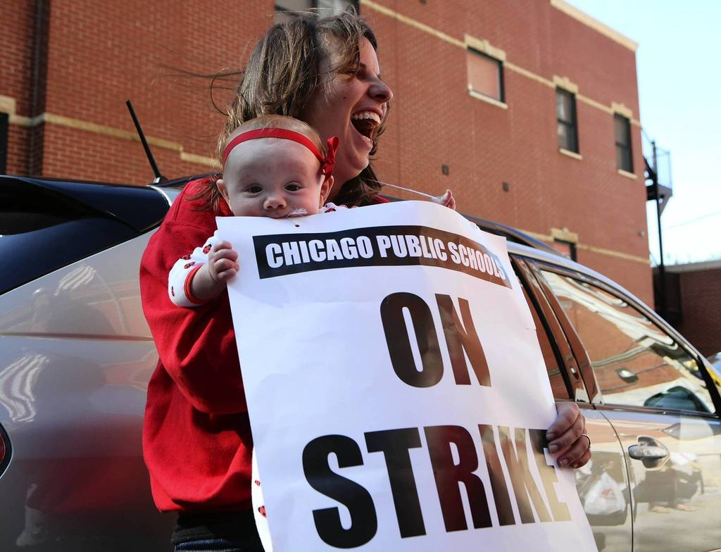 Six-month-old Adele Campbell takes a bite out of the strike sign held by special education teacher Meredith Bazzoli. Campbell is holding Adele for her mother Jessica Campbell, who is also a teacher. Chicago teachers and staff gathered with their strike signs outside of Galileo Scholastic Academy to start the second day of their strike