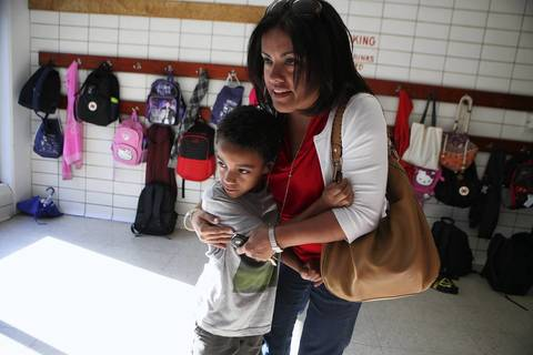 Elvia Bravo-White embraces her son Ethan White, 7, a second grader, as he surveys the room full of children at the Sheridan Park fieldhouse at 901 S. Aberdeen St. in Chicago. Over 100 grade school students were dropped off at the school for a Play in the Park, a program designed to help parents and guardians find activities for their children while Chicago teachers continue their strike.