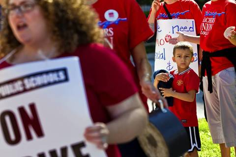 Student Leo Vera, 5, joins his mother Sarah Vera as Chicago Public Schools teachers walk picket lines near Dunbar Vocational Career Academy in Chicago on Tuesday. Vera is a teacher at Pershing West Middle School.