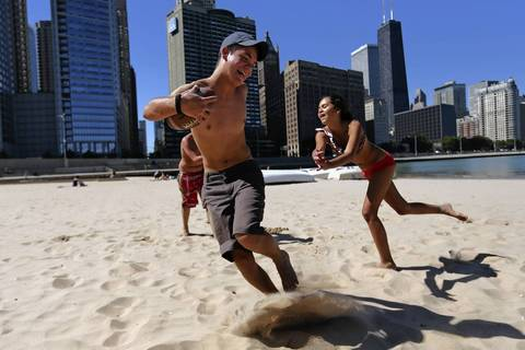 Chicago Public School junior Patrick Koegler, 17, and 8th grader Leona Belle Sansone 13, play football at Ohio Street Beach on day two of the teachers strike in Chicago.