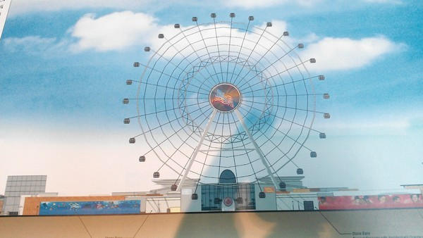 Rendering of the giant observation wheel proposed for I-Drive Live, with large circular sponsor/advertiser logo in middle of structure.