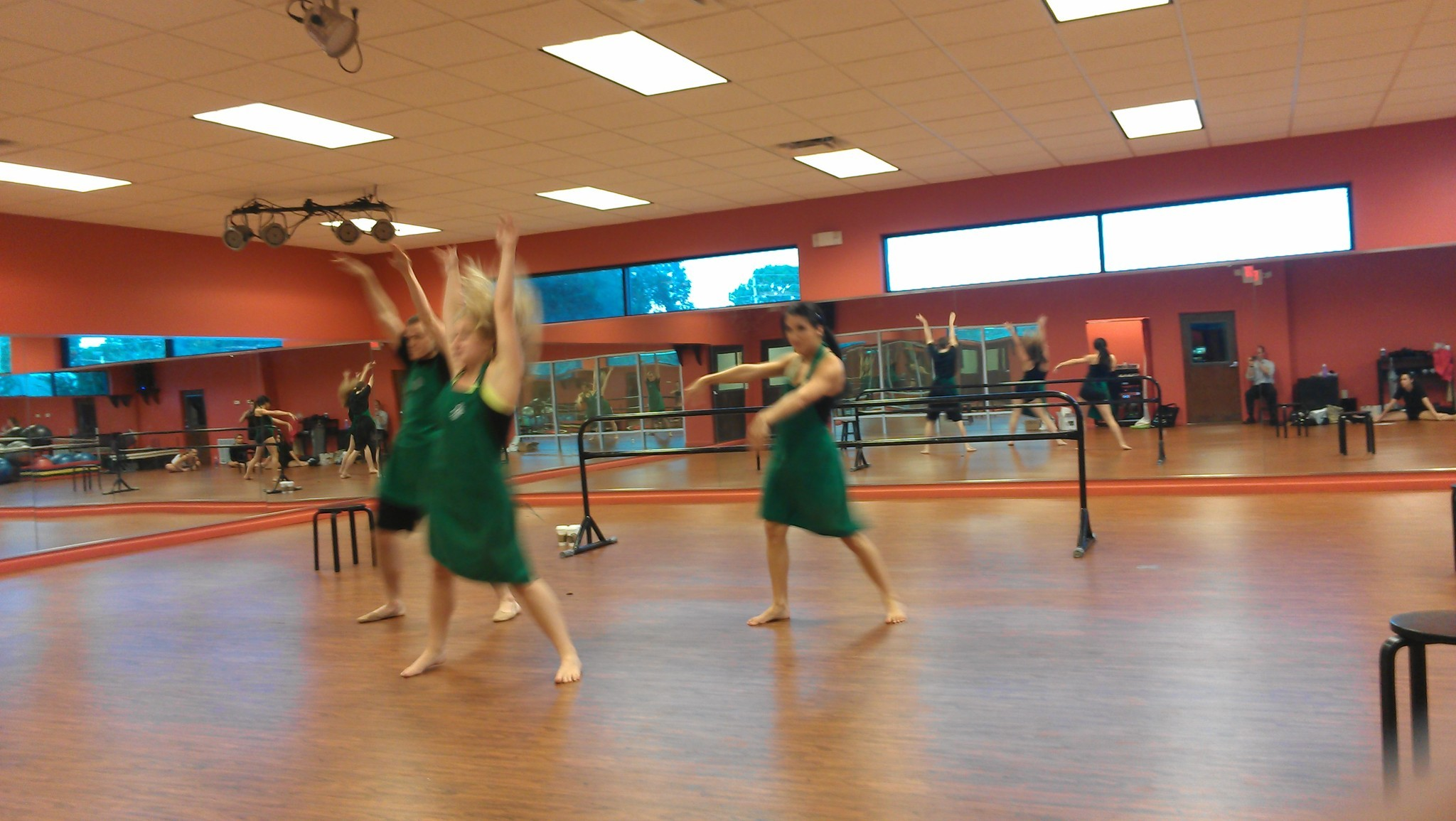 "Dancers dress in the familiar green aprons of Starbucks baristas as they rehearse a number from the Emotions Dance production of ""Blur."""