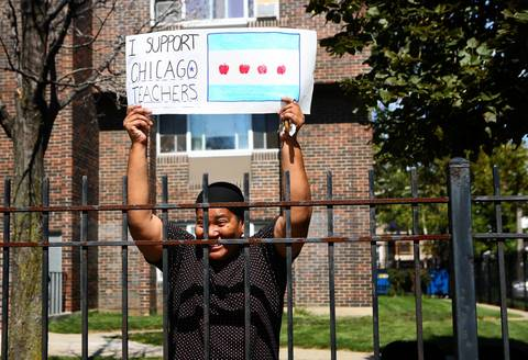 Neighbors cheer on Chicago Teachers Union members as they rally near Marshall High School on the West Side of Chicago.