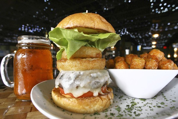 The Teak bistro burger is smothered with provolone cheese and served on a brioche bun with a slice of vine-ripe tomato, onion rings and tender lettuce.