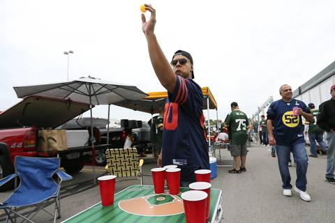 Bears fan Armando Flores plays beer pong before the Bears play the Packers.