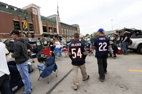 Bears fans walk through a Lambeau Field parking lot before the Bears play the Packers.