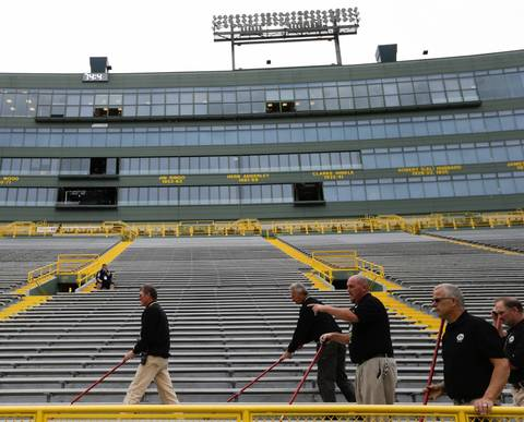 Workers sweep the stadium before the Green Bay Packers and Chicago Bears play at Lambeau Field.