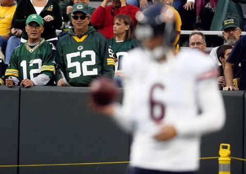 Packers fans watch as Bears quarterback Jay Cutler warms up.