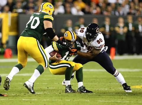 Julius Peppers sacks Green Bay quarterback Aaron Rodgers in the first quarter.