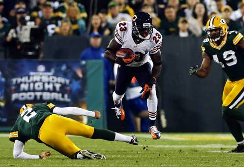 Devin Hester is tripped up by Packers kicker Mason Crosby on a kick return in the second quarter.