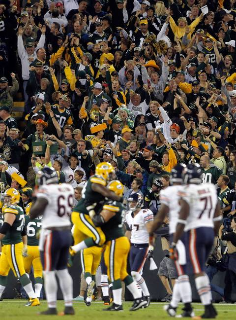 Packers fans celebrate a touchdown on a fake field goal play against the Bears in the second quarter.