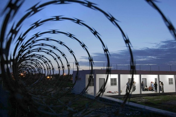 """Razor wire tops the chain-link fence around a church-run migrant shelter in Matamoros, Mexico, where 15 deportees were dragged away at gunpoint Christmas Eve. Serafin Salazar, who had been an auto mechanic in El Monte, said, """"I feel like something bad can happen at any time."""""""