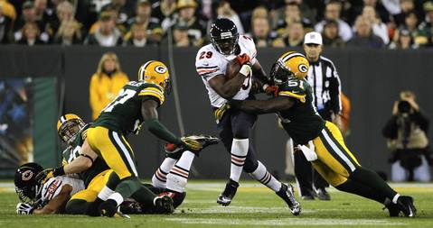 Running back Michael Bush is tackled by the Packers' D.J. Smith in the 4th quarter.