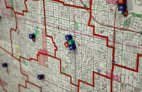 A map of the city hangs on a wall in the Los Angeles 911 call center with magnets marking dispatched units in various neighborhoods.