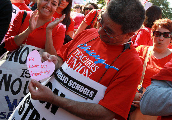 Francisco Perez receives a heart from a student as hundreds of CPS teachers, students and their supporters rally for teachers at the Logan Square monument on Friday.