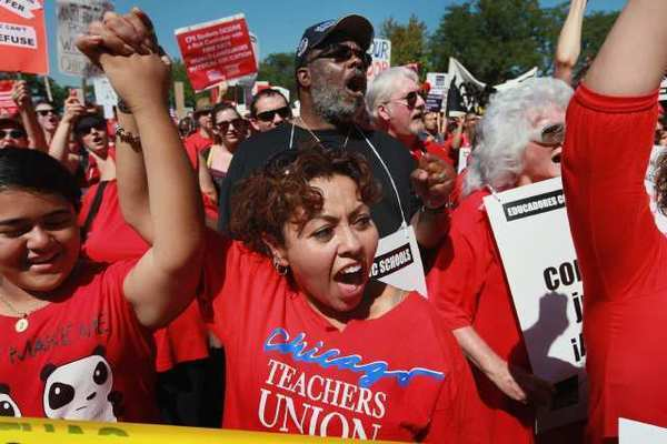 Striking teachers and their supporters rally at Union Park on Saturday in Chicago. The rally was a show of solidarity as negotiations on a labor contract continued.