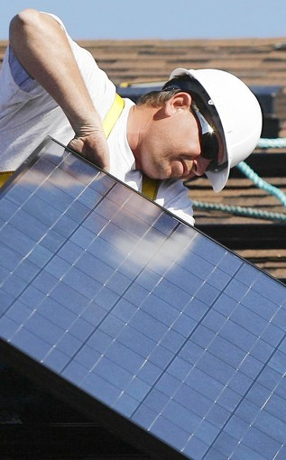 Steve Fleming, with BlueChip Energy of Lake Mary, installs solar panels at a model home in Apopka. Eustis officials want to sell city-owned property to BlueChip.